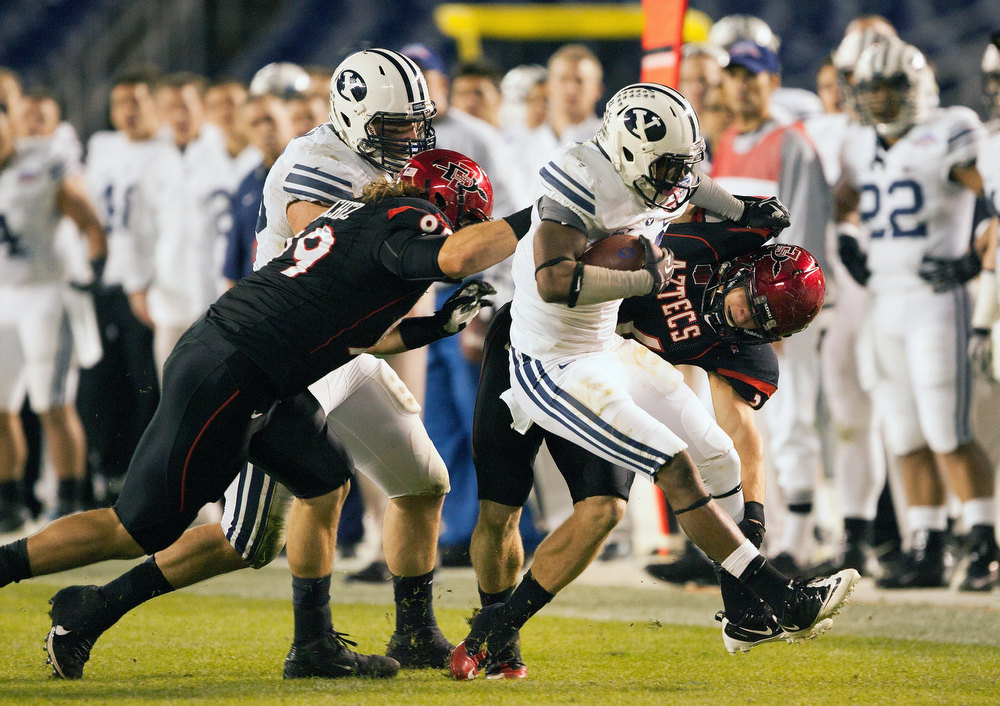 . DeQuan Everett #21 of the BYU Cougars runs with the ball in the first half of the game as Rene Siluano #39 and Hunter Hewitt #89 of the San Diego State Aztecs tackle in the Poinsettia Bowl at Qualcomm Stadium on December 20, 2012 in San Diego, California. (Photo by Kent C. Horner/Getty Images)