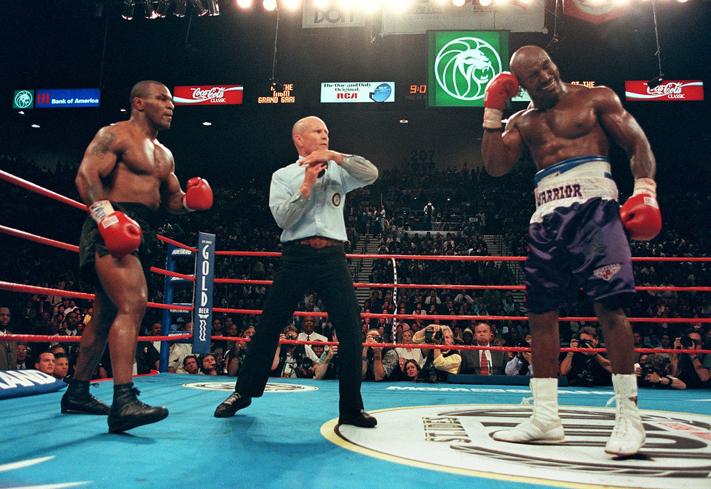 . Referee Lane Mills (C) stops the fight in the third round as Evander Holyfield (R) holds his ear as Mike Tyson (L) watches 28 June 1997 during their WBA heavyweight championship fight at the MGM Grand Garden Arena in Las Vegas, NV. Holyfield won by disqualification in the the third round after Tyson bit his ear.    (JEFF HAYNES/AFP/Getty Images)