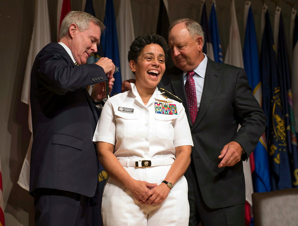 . In a Photo provided by the U.S. Navy,  Adm. Michelle Howard, center, smiles as Secretary of the Navy Ray Mabus, left, and Wayne Cowles, Howard\'s husband, put four-star shoulder boards on Howard\'s service white uniform during her promotion ceremony at the Women in Military Service for America Memorial in Washington Tuesday July 1, 2014. Howard is the first woman to be promoted to the rank of admiral in the history of the Navy and will assume the duties and responsibilities as the 38th Vice Chief of Naval Operations from Adm. Mark Ferguson. (AP Photo/U.S. Navy, Chief Mass Communication Specialist Peter D. Lawlor)