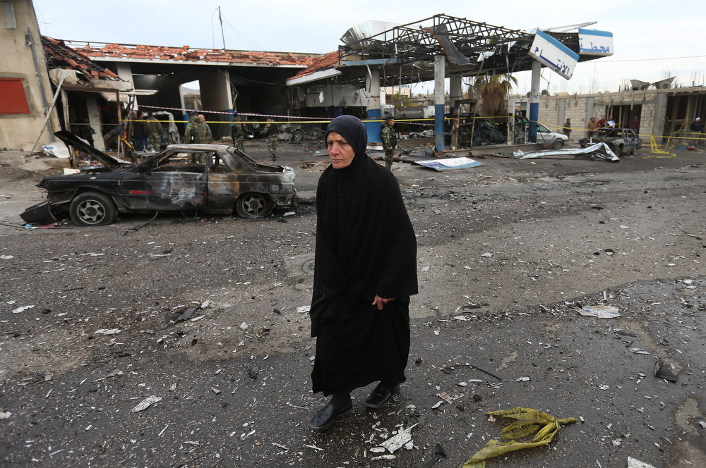 . A Lebanese woman passes by the site of a deadly car bomb that exploded Saturday evening near a gas station, in the predominately Shiite town of Hermel, about 10 miles (16 kilometers) from the Syrian border in northeast Lebanon, Sunday, Feb. 2, 2014.  (AP Photo/Hussein Malla)