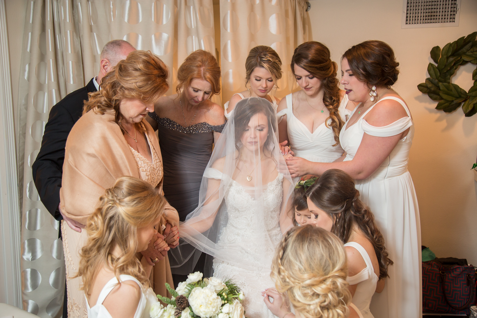 A bride praying with her family before her wedding ceremony