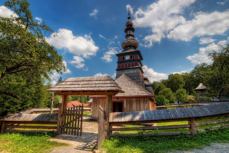 Entry to a wooden church  The open gate on this church looked so welcoming, but the inside was closed of with a gate. But anyway it still looked great :). This is one of the two churches in the open air museum in Bardejovske Kupele (from which I have already uploaded a few photos :)). I haven't found the name of this one, only that it's originally from the village Zbroj, from where it was moved in 1967.   HDR from three shots, taken with Canon 450D with Sigma 10-20mm lens, from a tripod.