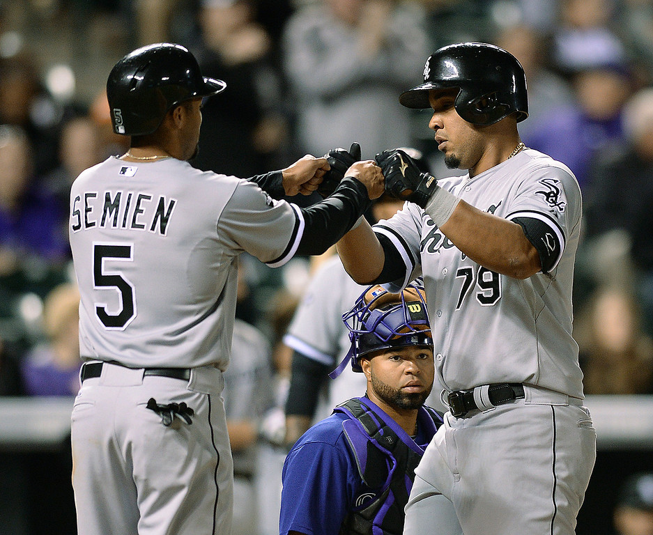 . Chicago slugger Jose Abreu (79) was met at the plate by teammate Marus Semien (5) following an eighth inning home run off Colorado reliever Wilton Lopez.  (Photo by Karl Gehring/The Denver Post)