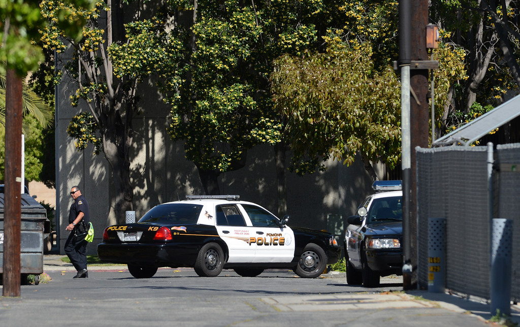. Pomona Police and LA County Sheriff\'s Bomb Squad officials investigate the scene of a suspicious package Thursday, April 18, 2013, at the corner of W Mission Blvd and S Main Street in Pomona. Jennifer Cappuccio Maher/Staff Photographer