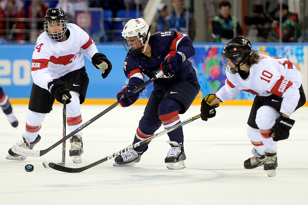 . Kelli Stack (16) of the U.S.A. controls the puck as Nicole Bullo (10) of the Switzerland and Evelina Raselli (14) defends during the second period of action at the Shayba Arena. Sochi 2014 Winter Olympics on Monday, February 10, 2014. (Photo by AAron Ontiveroz/The Denver Post)