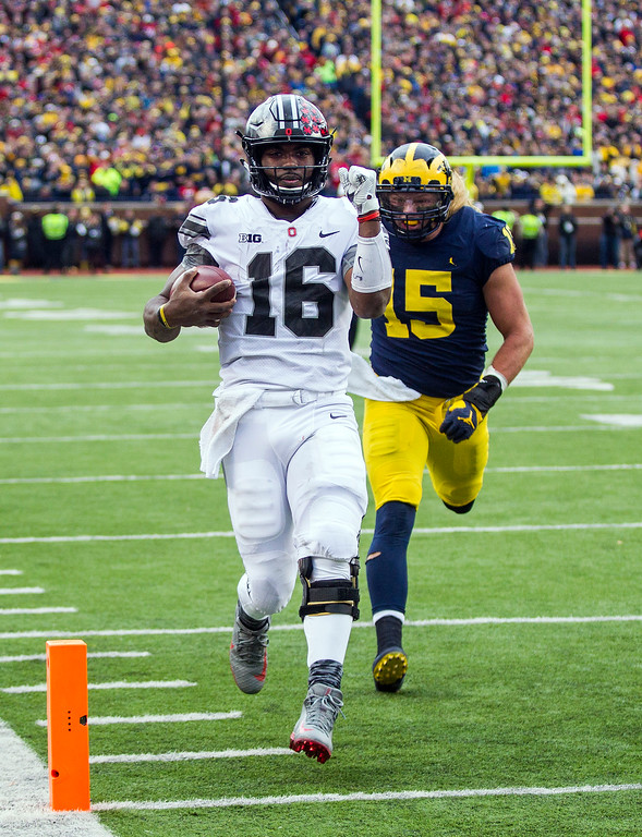 . Ohio State quarterback J.T. Barrett (16) scores a touchdown, defended by Michigan defensive lineman Chase Winovich (15), in the second quarter of an NCAA college football game in Ann Arbor, Mich., Saturday, Nov. 25, 2017. (AP Photo/Tony Ding)