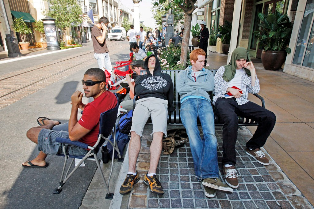 . Ismail Elshareef, left, James Michael sleeping, Kyle Lorez, second right, and David Elsenbroich have been waiting in line since 5 a.m. to buy the Apple iPhone outside the Apple store at The Grove outdoor shopping mall in Los Angeles, Friday, June 29, 2007. After six months of hype, thousands of people Friday will get their hands on the iPhone, the new cell phone that Apple Inc. is banking on to become its third core business next to its moneymaking iPod players and Macintosh computers. Customers were camped out at Apple and AT&T stores across the nation. The gadget, which combines the functions of a cell phone, iPod media player and wireless Web browser, will go on sale in the United States at 6 p.m. in each time zone. (AP Photo/Kevork Djansezian)
