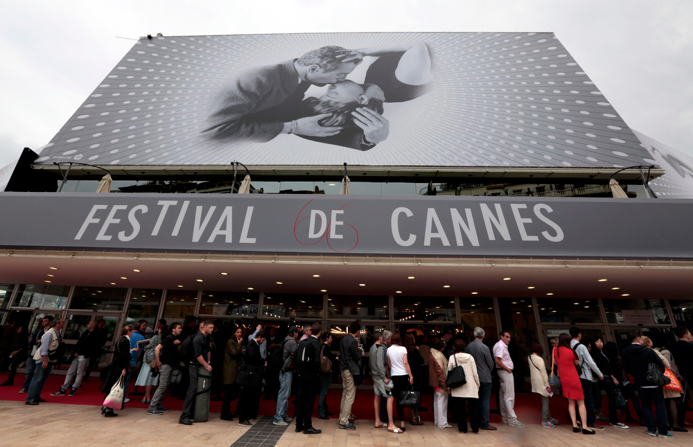 . Visitors wait to enter in the Festival Palace covered by a giant canvas of the official poster of the 66th Cannes Film Festival in Cannes May 15, 2013. The 66th Cannes Film Festival will run from May 15 to May 26.     REUTERS/Eric Gaillard