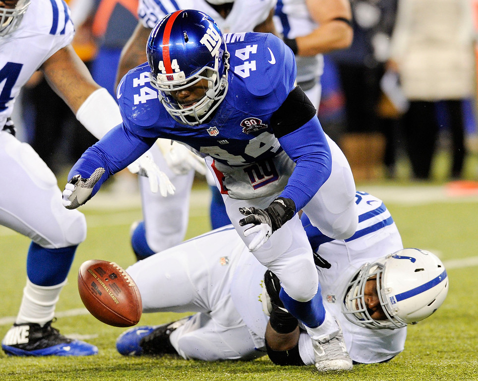 . New York Giants running back Andre Williams (44) fumbles the ball as he is hit by Indianapolis Colts nose tackle Josh Chapman (96) during the first half of an NFL football game Monday, Nov. 3, 2014, in East Rutherford, N.J. The Giants recovered the ball on the play. (AP Photo/Bill Kostroun)