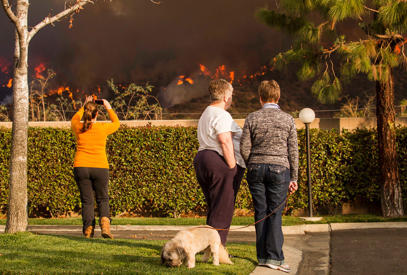 . Local residents watch the fire at their back yard as a wildfire burns just north of the San Gabriel Valley community of Glendora, Calif., on Thursday, Jan 16, 2014. Southern California authorities have ordered the evacuation of homes at the edge of a fast-moving wildfire burning in the dangerously dry foothills of the San Gabriel Mountains. (AP Photo/Ringo H.W. Chiu)