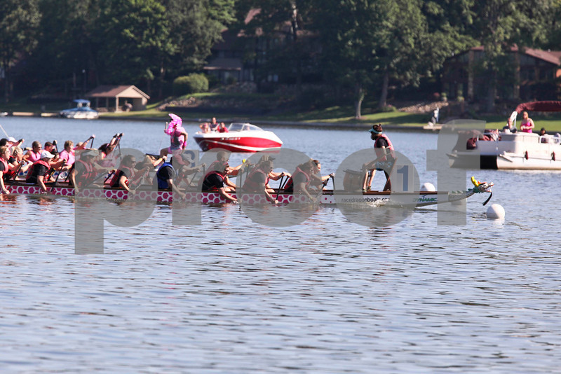 "A trio of boats cross the finish line at the Portage Lakes Dragon boat festival a the Portage Lakes State Park in New Franklin, Ohio on July 13 2013.  The activities started down an the beach with a ceremonial eye-dotting ""awakening of the dragons and  three dragon boat teams headed to the finish line every few minutes.  Lew Stamp Photography."