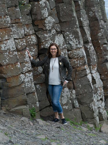 Woman standing near basalt rocks, Giants Causeway, County Antrim, Northern Ireland, United Kingdom