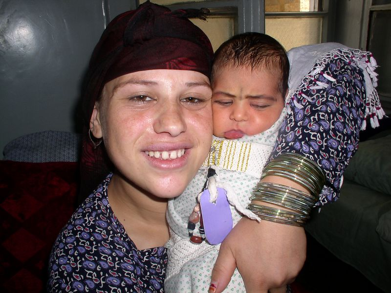"""This is young mother is deaf as a result of  bombing when she was 5 years old. Despite her disability and illiteracy, her smile and non-verbal communication are incredible. Below is a picture of her baby in the """"Afghani net""""."""