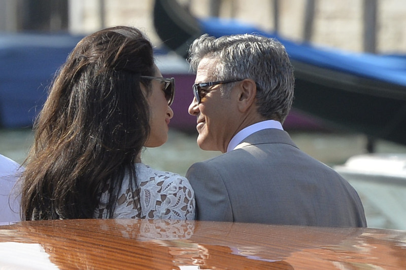 """. US actor George Clooney (R) and his wife Amal Alamuddin stand on a taxi boat on the Grand Canal on September 28, 2014 in Venice. Hollywood heartthrob George Clooney and Lebanese-British lawyer Amal Alamuddin married in Venice on Saturday September 27, 2014 before partying the night away with their A-list friends in one of the most high-profile celebrity weddings in years. \""""George Clooney and Amal Alamuddin were married today (September 27) in a private ceremony in Venice, Italy,\"""" Clooney spokesman Stan Rosenfield said. The announcement came as a surprise as the pair were not expected to officially tie the knot until Monday, though they are still tipped for a civil ceremony at the town hall to make the marriage official under Italian law. ANDREAS SOLARO/AFP/Getty Images"""