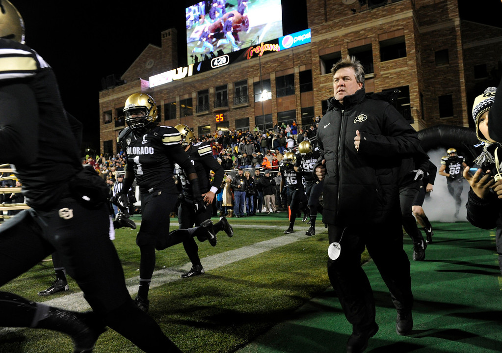 . BOULDER, CO - NOVEMBER 23: Senior Derrick Webb (1), a linebacker for the Colorado Buffaloes football team, helps lead the team on to Folsom Field alongside CU head coach Mike MacIntyre, right, following famed live-buffalo mascot Ralphie in the game against the Southern California Trojans at Folsom Field in mid-November. (Photo by Kathryn Scott Osler/The Denver Post)