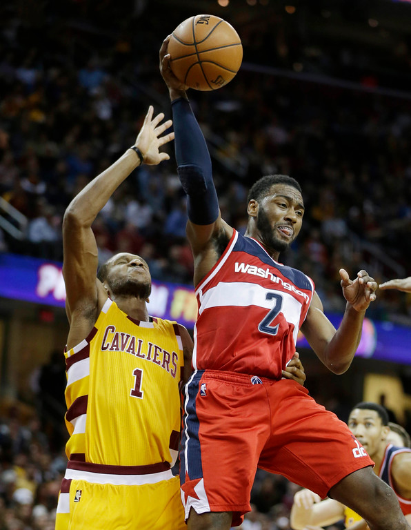 . Washington Wizards\' John Wall (2) passes in front of Cleveland Cavaliers\' James Jones (1) in the second half of an NBA basketball game Tuesday, Dec. 1, 2015, in Cleveland. The Wizards won 97-85. (AP Photo/Tony Dejak)
