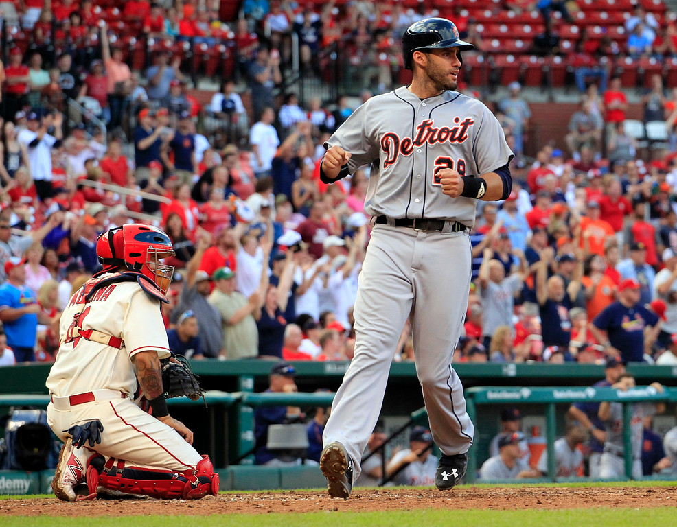 . Detroit Tigers\' J.D. Martinez, right, pumps his fist as he scores past St. Louis Cardinals catcher Yadier Molina during the 10th inning of a baseball game Saturday, May 16, 2015, in St. Louis. The Tigers won 4-3. (AP Photo/Jeff Roberson)