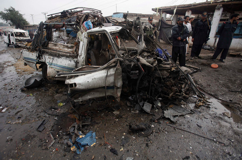 . Security forces stand near a car which was damaged during a bomb attack at Fauji Market in Peshawar December 17, 2012. The blast in the market in northwest Pakistan on Monday killed at least 15 people, a security official said. The official said at least 20 people had been wounded in the blast in the market in the Khyber region, near the border with Afghanistan, and the death toll could rise.   REUTERS/Fayaz Aziz