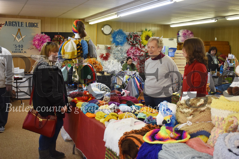 "Joy Claypoole, right, of West Sunbury, looks over the afghans and handmade other crocheted items for sale by Lana Swartzland, middle, who had a booth with her daughter, Donna Crawford, both of Chicora, at Masonic Lodge on Chicora Road as part of the annual Christmas in Chicora Christmas in Chicora event organized by Quality Life Services in Chicora. The two-day event will featured activities throughout downtown and surrounding Chicora and showcased the businesses and people of the tight-knit community. The Masonic Lodge was one of more than 20 stops along the way where participants could get the ""passport"" stamped."