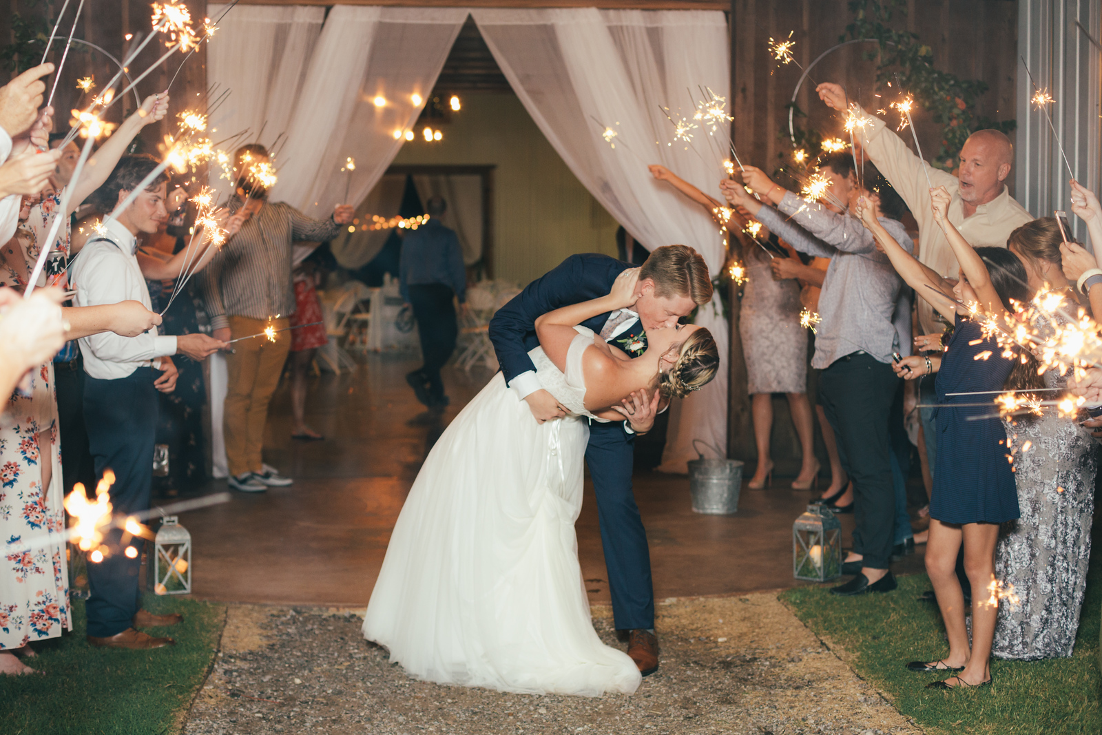 newlywed couple kissing as the groom dips the bride as they are surrounded by their wedding guests holding sparklers