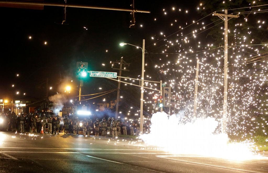 . A device deployed by police goes off in the street as police and protesters clash Wednesday, Aug. 13, 2014, in Ferguson, Mo. Authorities in the St. Louis suburb where an unarmed black teen was shot and killed by a police officer have used tear gas to try to disperse protesters after flaming projectiles were thrown from the crowd. (AP Photo/Jeff Roberson)