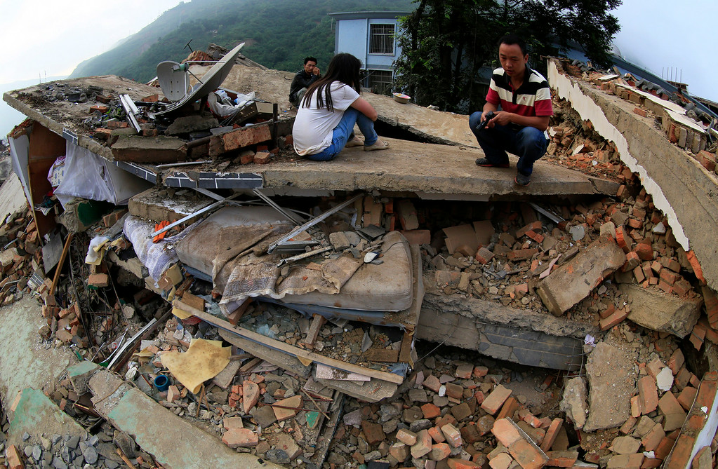 . In this photo provided by China\'s Xinhua News Agency, people sit on the ruins of a house, damaged by a strong earthquake in Longtoushan township of Ludian county, southwest China\'s Yunnan Province, Tuesday, Aug. 5, 2014.   (AP Photo/Xinhua, Zhang Guangyu)