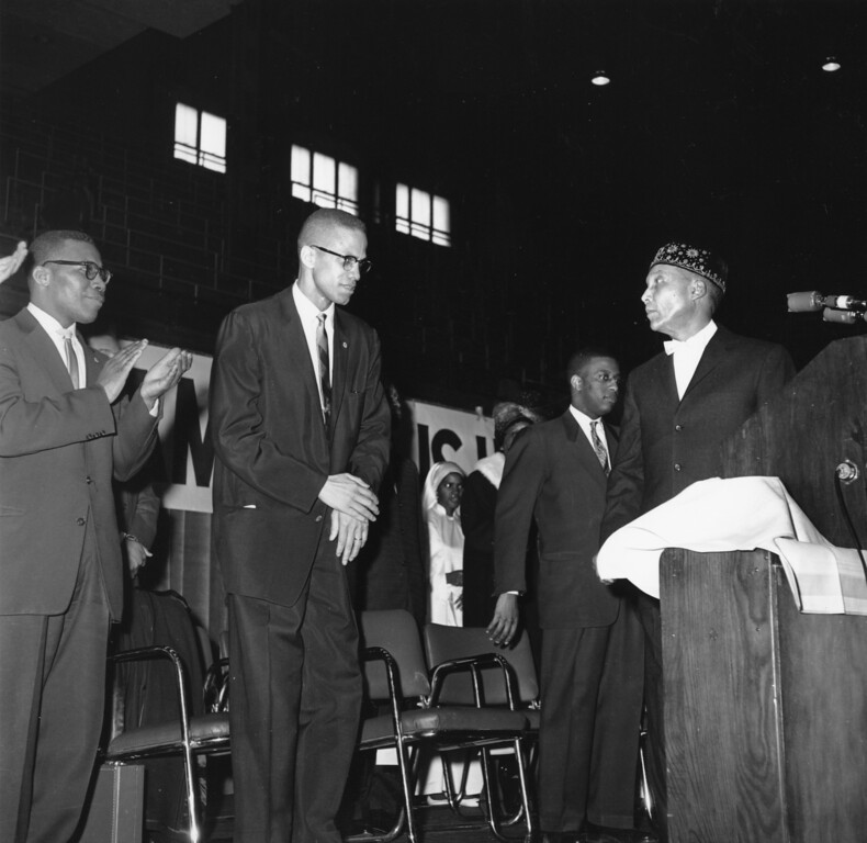 . Elijah Muhammad, founder and head of the Nation of Islam, is shown at a lecturn in Chicago introducing Malcolm X on  Feb. 26, 1961.  (AP Photo/Paul Cannon)