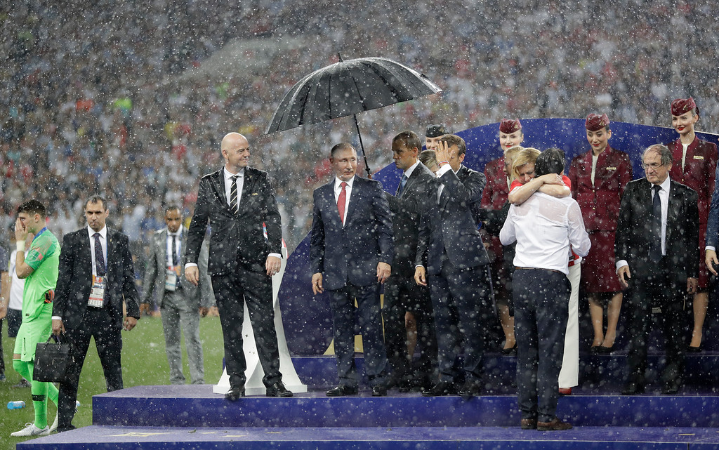 . FIFA President Gianni Infantino, third left, gestures as Russian President Vladimir Putin stands underneath an umbrella as Croatian President Kolinda Grabar-Kitarovic greets Croatia head coach Zlatko Dalic after the final match between France and Croatia at the 2018 soccer World Cup in the Luzhniki Stadium in Moscow, Russia, Sunday, July 15, 2018. France won the final 4-2. (AP Photo/Matthias Schrader)