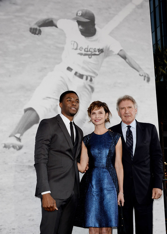 """. Actors Chadwick Boseman, Calista Flockhart and Harrison Ford arrive at the premiere of Warner Bros. Pictures\' and Legendary Pictures\' \""""42\"""" at the Chinese Theatre on April 9, 2013 in Los Angeles, California.  (Photo by Kevin Winter/Getty Images)"""