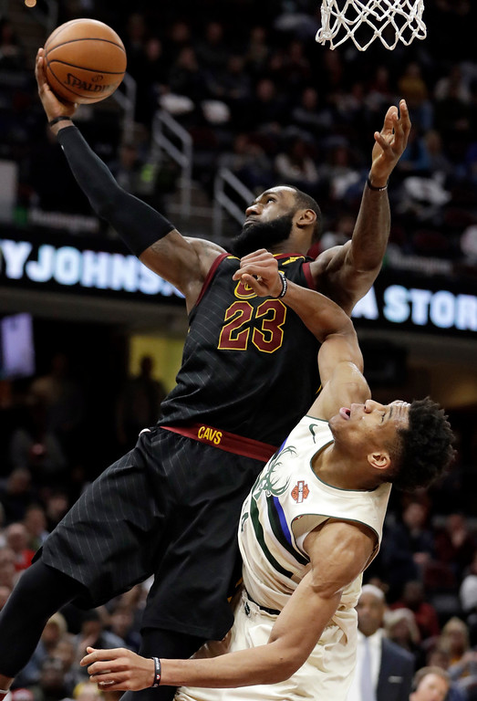 . Cleveland Cavaliers\' LeBron James, top, grabs a rebound ahead of Milwaukee Bucks\' Giannis Antetokounmpo, from Greece, in the second half of an NBA basketball game, Monday, March 19, 2018, in Cleveland. (AP Photo/Tony Dejak)