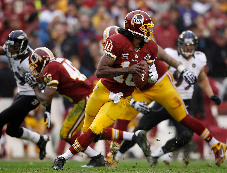 . Washington Redskins quarterback Robert Griffin III (C) rolls out of the pocket against the Baltimore Ravens in the second half of their NFL football game in Landover, Maryland December 9, 2012.     REUTERS/Gary Cameron   (UNITED STATES - Tags: SPORT FOOTBALL)