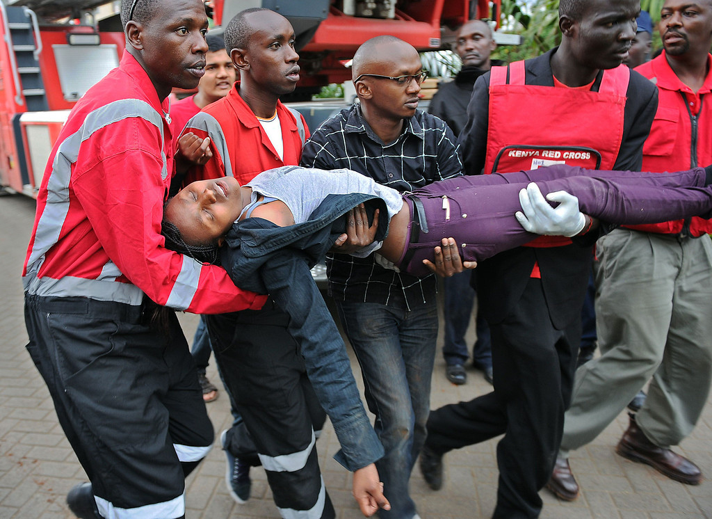 . A woman who had been held hostage is carried in shock by rescue personnel on September 21, 2013, after she was freed following a security operation at an upmarket shopping mall in Nairobi where suspected terrorists engaged Kenyan security forces in a drawn out gun fight. Some 20 people have been killed and about 50 wounded Saturday in the initial attack by the gunmen the Kenya Red Cross said.  AFP PHOTO / Tony KARUMBA/AFP/Getty Images