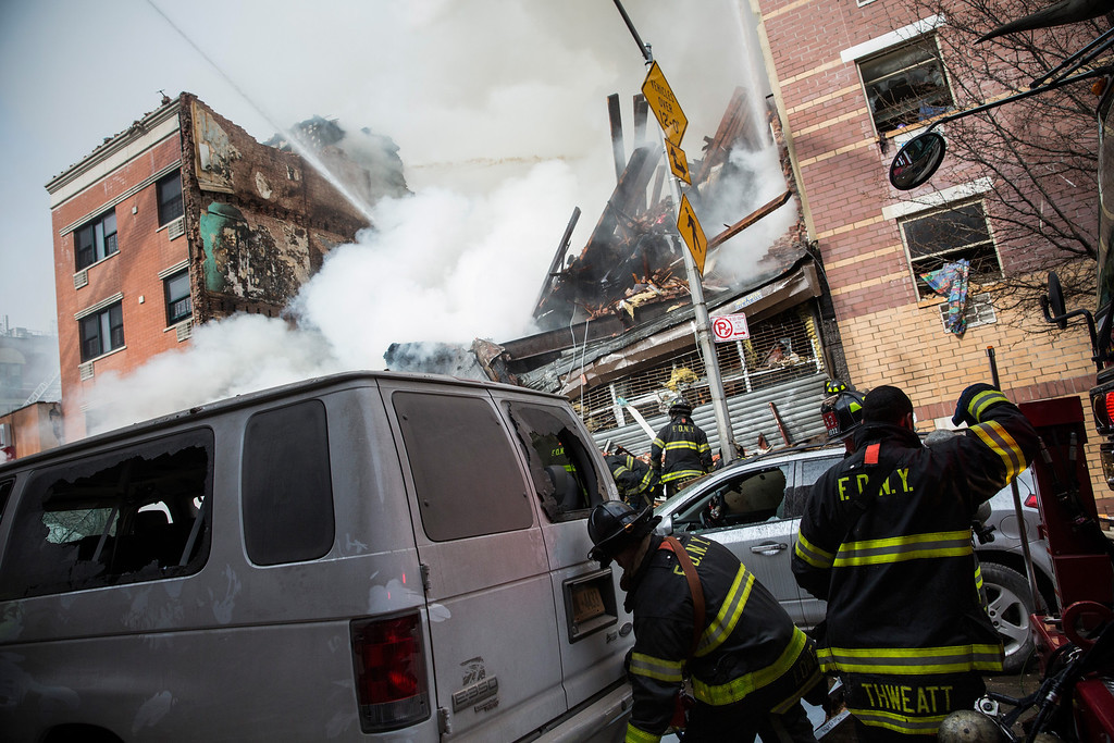 . Firefighters from the Fire Department of New York (FDNY) respond to a 5-alarm fire and building collapse at 1646 Park Ave in the Harlem neighborhood of Manhattan March 12, 2014 in New York City. Reports of an explosion were heard before the collapse of two multiple-dwelling buildings that left at least 11 injured.  (Photo by Andrew Burton/Getty Images)