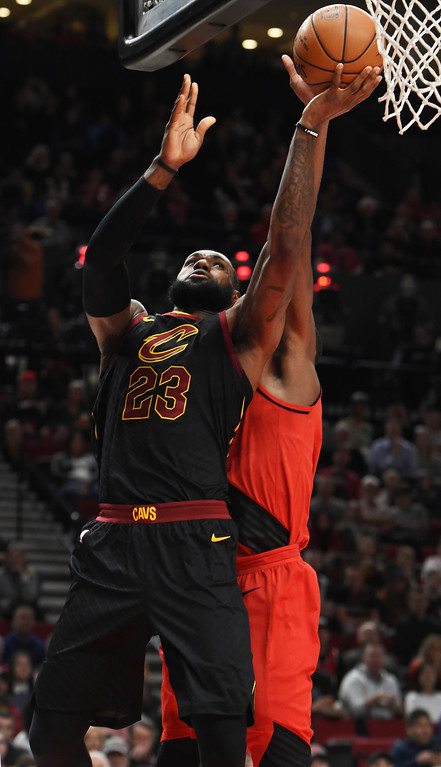 . Cleveland Cavaliers forward LeBron James, left, drives to the basket on Portland Trail Blazers forward Ed Davis, left, during the first half of an NBA basketball game in Portland, Ore., Thursday, March 15, 2018. (AP Photo/Steve Dykes)