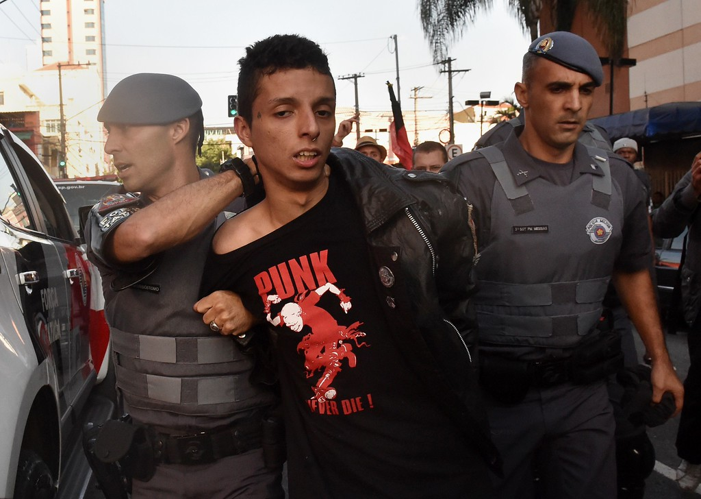 . Riot police arrest a protester (C) in Sao Paulo on June 12, 2014, at the beginning of the 2014 FIFA World Cup.  AFP PHOTO / RODRIGO  ARANGUA/AFP/Getty Images