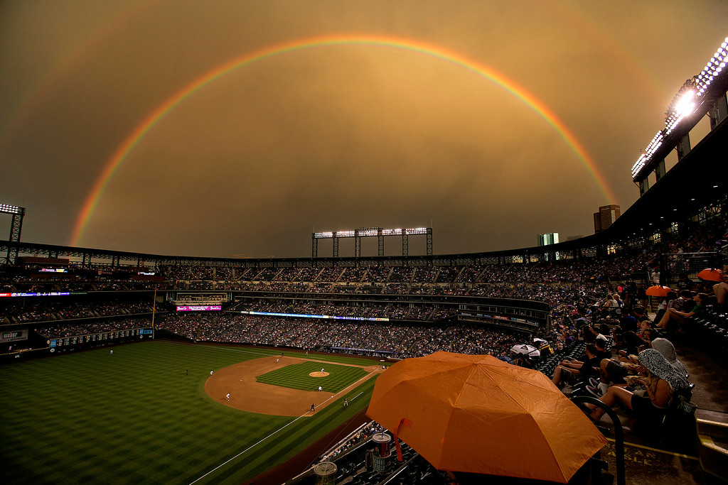 . Fans sit under the cover of an umbrella as a rainbow illuminates the field while starting pitcher Brett Anderson #30 of the Colorado Rockies delivers to home plate during the fifth inning against the Pittsburgh Pirates at Coors Field on July 25, 2014 in Denver, Colorado. (Photo by Justin Edmonds/Getty Images)