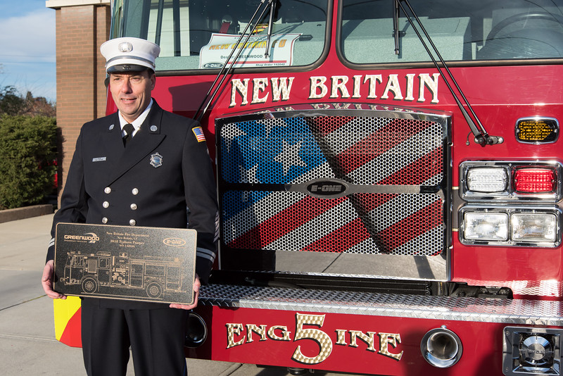 11/14/18  Wesley Bunnell | Staff  The New Britain Fire Department unveiled three new fire trucks on Wednesday afternoon during a ceremony at their Beaver St headquarters. Captain Paul Couture holds a plaque of Engine 5 while posing for a photo.