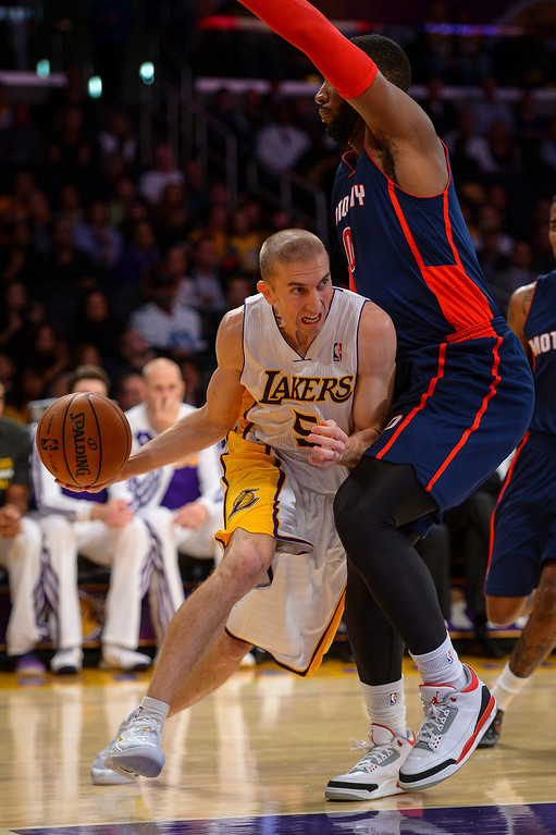 . Lakers� Steve Blake drives around Detroit�s Andre Drummond during first half action at Staples Center Sunday, November 17, 2013.  ( Photo by David Crane/Los Angeles Daily News )
