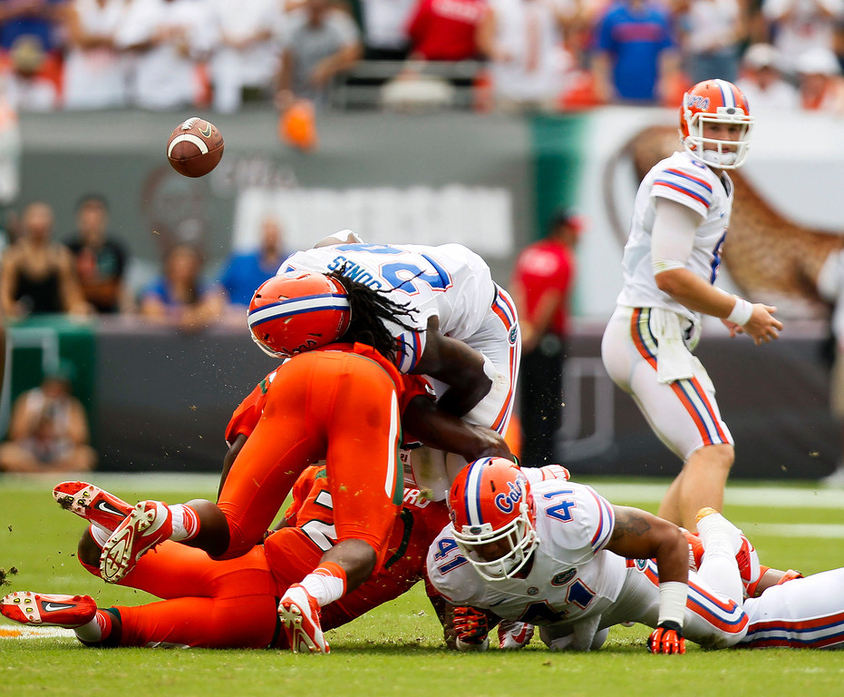 . Florida Gators running back Matt Jones (24) fumbles the ball against Miami during the first half of an NCAA college football game in Miami Gardens, Fla., Saturday, Sept. 7, 2013. Miami defeated Florida 21-16.  (AP Photo/The Tampa Bay Times, Will Vragovic)