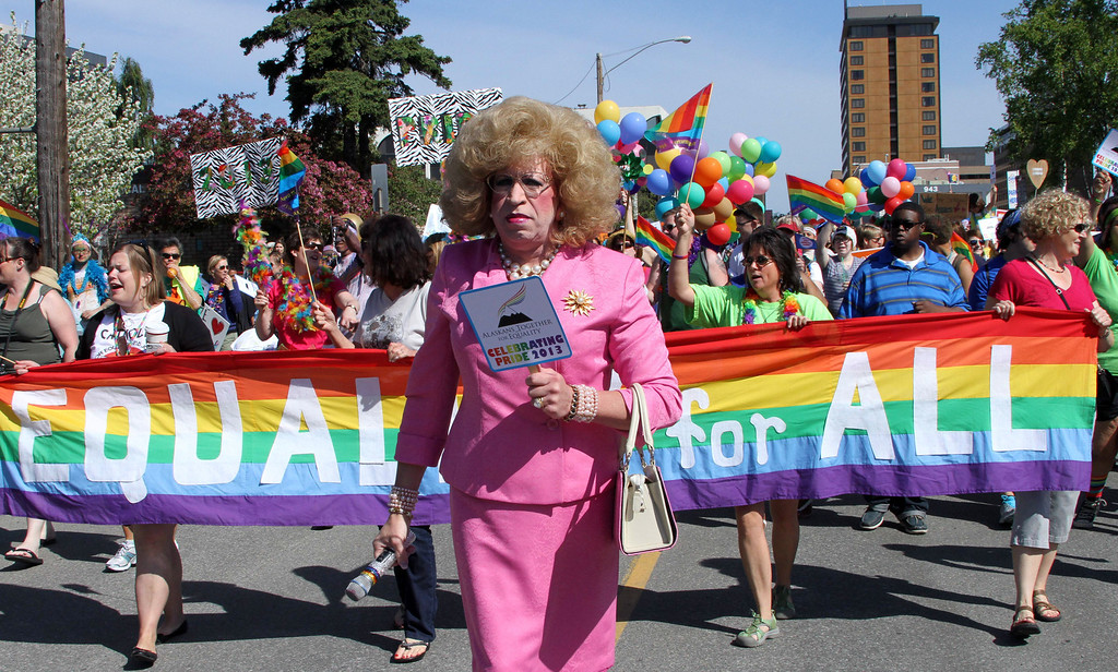 . Scott Koeller, known as Daphne DoALL LaChores, helps lead participants during the Alaska Pride March in downtown Anchorage on Saturday, June 15, 2013. Instead of  parade, a unity march was held from downtown to the Alaska Pride Festival on the Delaney Park Strip. (AP Photo/Mark Thiessen)