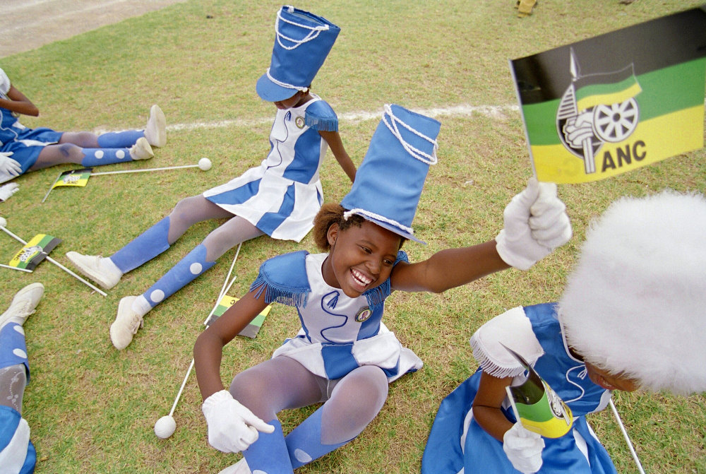 Description of . South African majorettes rest 25 March 1994 during an African National Congress (ANC) election rally at Kollekoberg stadium in Graaf Reinet, prior to a scheduled appearence by Nelson Mandela. (Photo credit should read ALEXANDER JOE/AFP/Getty Images)