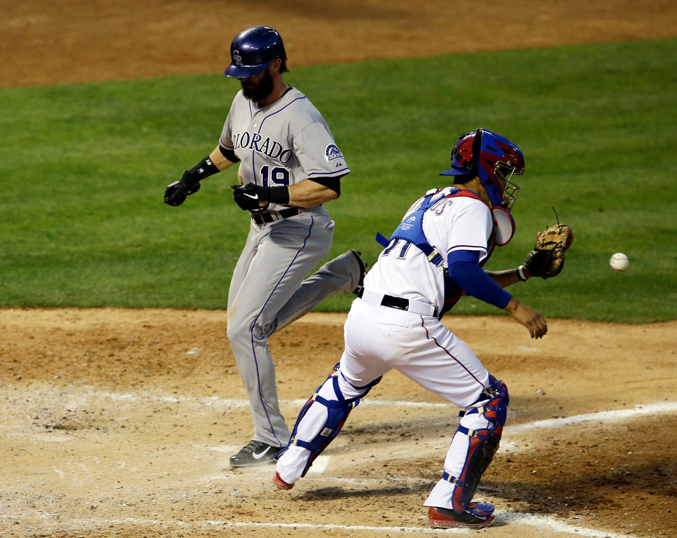 . Colorado Rockies\' Charlie Blackmon scores ahead of the throw to Texas Rangers catcher Robinson Chirinos, right, on a sacrifice fly out by Rockies\' Troy Tulowitzki in the fourth inning of a baseball game, Wednesday, May 7, 2014, in Arlington, Texas. (AP Photo/Tony Gutierrez)