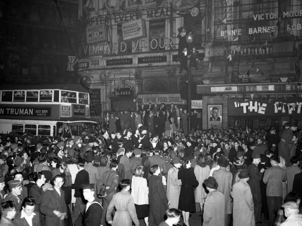 . British civilians and Allied service men and women gather, as part of a huge crowd, at London\'s Piccadilly Circus, May 7, 1945, to celebrate victory night. The revellers climbed lampposts, traffic lights and cars in their excitement. (AP Photo/Leslie Priest)