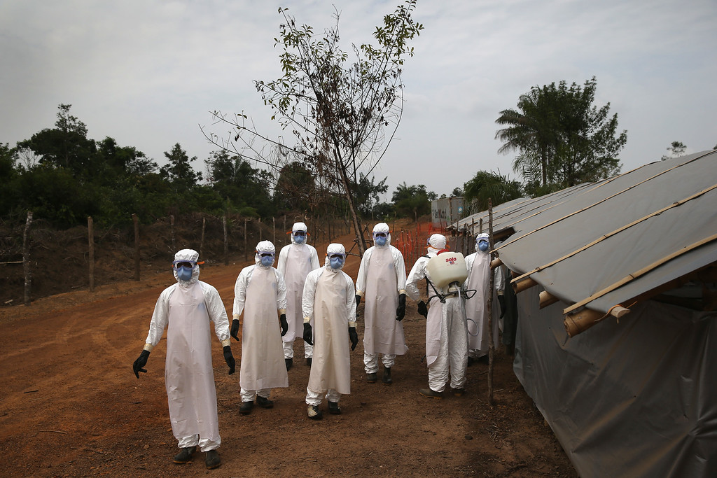 ". A burial team awaits decontamination at the U.S.-built cemetery for ""safe burials\"" on January 27, 2015 in Disco Hill, Liberia.  (Photo by John Moore/Getty Images)"