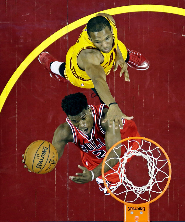 . Chicago Bulls\' Jimmy Butler, bottom, scores in front of Cleveland Cavaliers\' James Jones during the second half of Game 2 in a second-round NBA basketball playoff series Wednesday, May 6, 2015, in Cleveland. The Cavaliers defeated the Bulls 106-91. (AP Photo/Tony Dejak)
