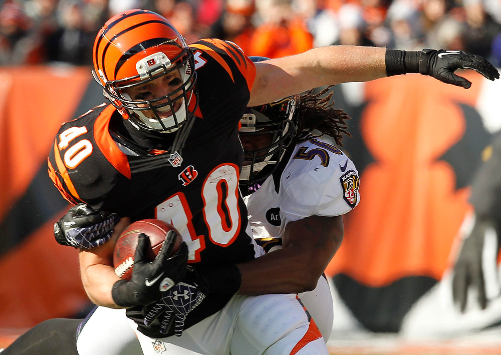 . Cincinnati Bengals\' Brian Leonard (40) is tackled by Baltimore Ravens\' Josh Bynes during the first half of play in their NFL football game at Paul Brown Stadium in Cincinnati, Ohio, December 30, 2012.      REUTERS/John Sommers II