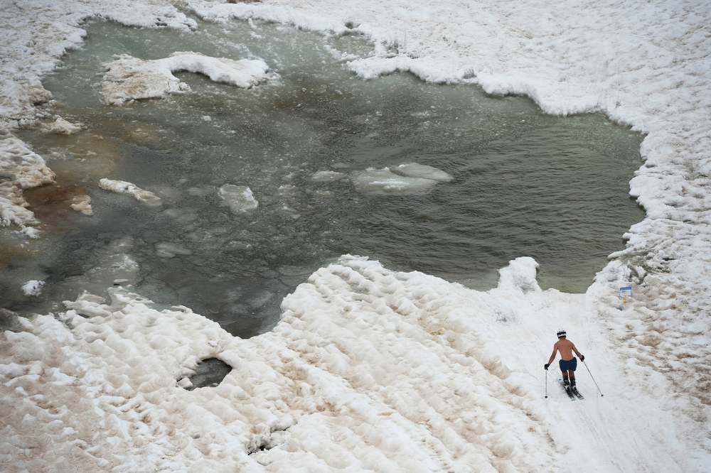 . A shirtless skier approaches the icy pond midway up the Arapahoe Basin ski area, near the Lenawee lift Saturday, June 21, 2014, the first day of summer. Arapahoe Basin closes for the 2013/14 ski season Sunday, June 22, 2014. (Photo By Andy Cross / The Denver Post)