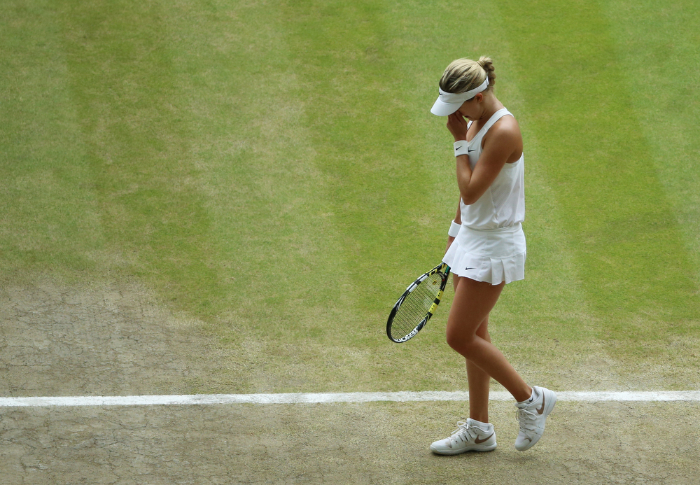 Description of . Eugenie Bouchard of Canada puts her hand to her face as she reacts to losing a point against Petra Kvitova of Czech Republic during the women\'s singles final at the All England Lawn Tennis  Championships at Wimbledon, London, Saturday, July, 5, 2014. (AP Photo/Gareth Fuller, Pool)