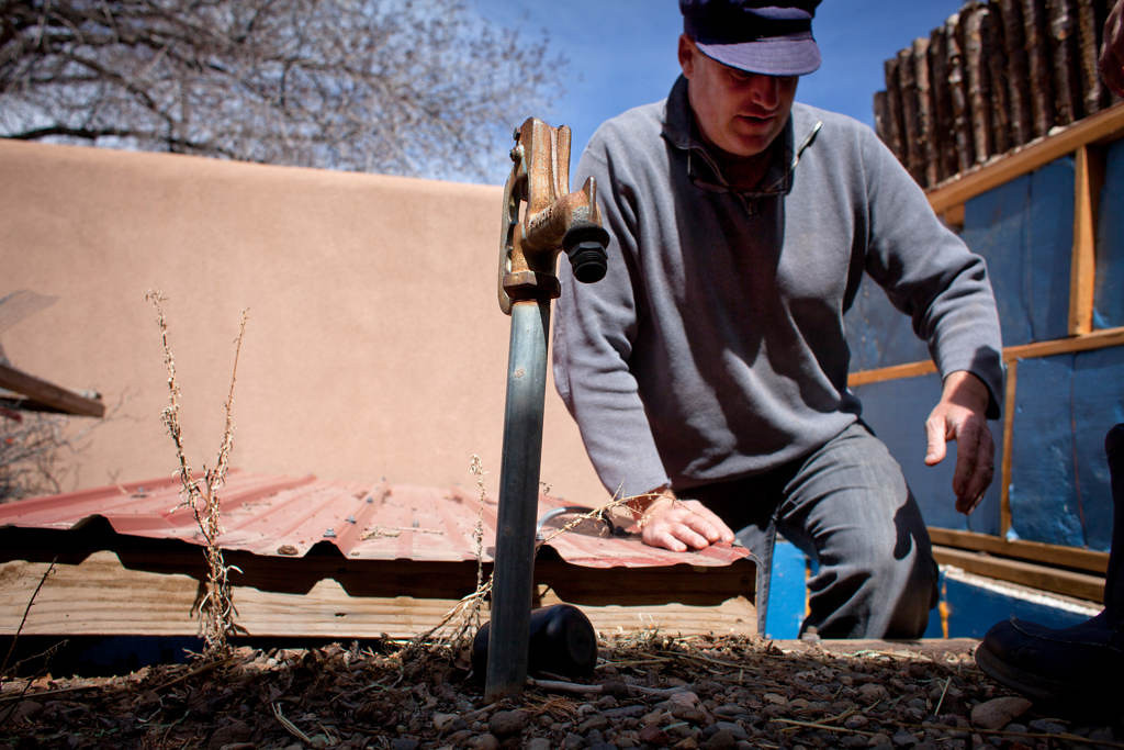 . Nate Downey emerges from a below-ground control center for the irrigation system at his home. The irrigation system is designed to target zones in the yard according to plant types, including trees, shrubs, vegetables and perennials. Plants can be watered according to their specific need, depending on the season and drought conditions.  (Special to the Pioneer Press: Mark Holm)