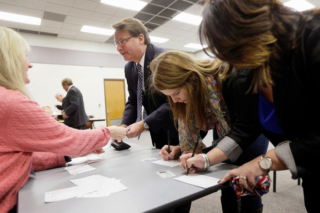 . Michigan Democratic Senate candidate Gary Peters, his daughter Madeleine, center, and his wife Colleen sign in to vote in Bloomfield Hills, Mich., Tuesday, Nov. 4, 2014. Peters is running against Republican Terri Lynn Land for the seat of retiring Democrat Carl Levin. (AP Photo/Carlos Osorio)